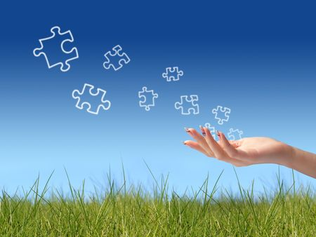 Puzzle game. Puzzle and hand over blue sky background.