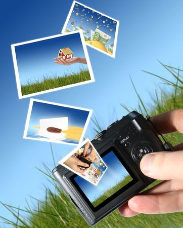 Camera and a lot of pictures. Sky and grass on the background. photo