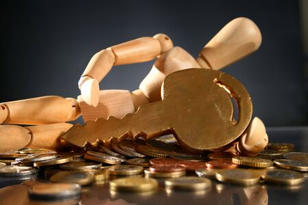 Wooden man, golden key and lot of coins. photo