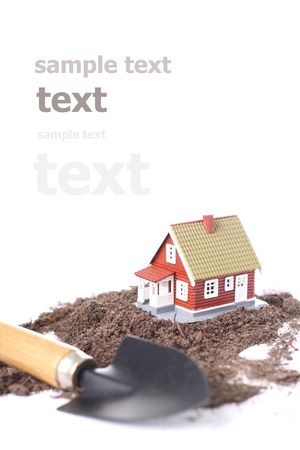 Little house and spadel with a wood handle isolated over a white background. photo