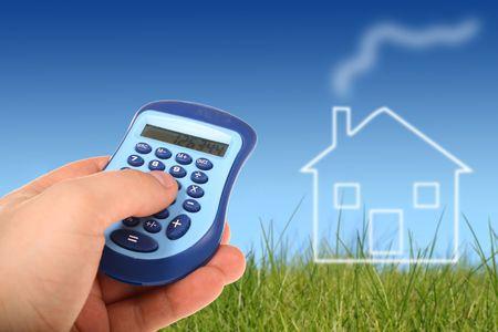 investment real state: Mano con calculadora y casa en el fondo.