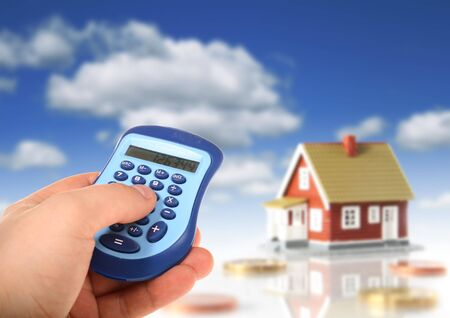 Hand with calculator and house on the background. photo
