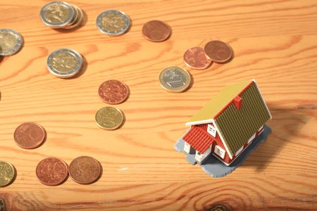 Little house and money over wood background. photo