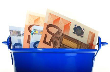 bucket of money: Euro money inside the bucket. Isolated over white.