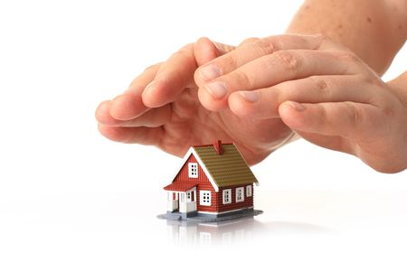 house insurance: House insurance. Hands and small house over white. Stock Photo