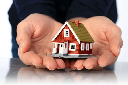 property development: Hands and small house. Real estate or insurance concept.