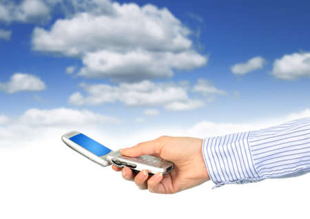 Cell phone in hand. Over blue sky background. Stock Photo - 7023726