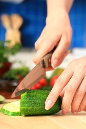 kitchen knife: Female chopping food ingredients on the kitchen.