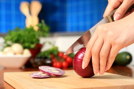 Female chopping food ingredients on the kitchen.