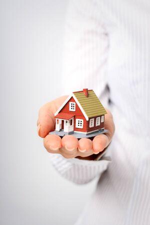 agent de s�curit�: Main donnant une petite maison.