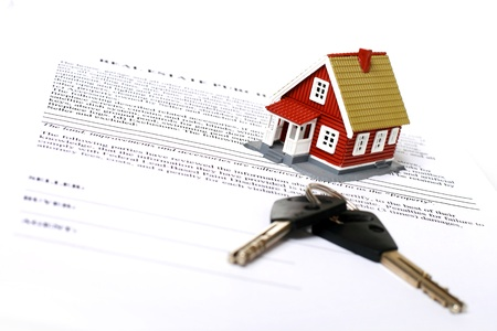 Real estate concept. Keys, money, small house and contract over white. Stock Photo