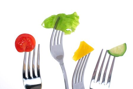Vegetables on forks isolated over white background.