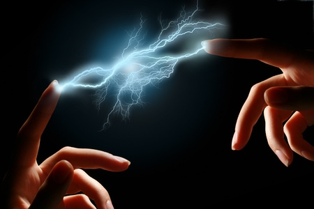 Hands and electric discharge over black background. photo