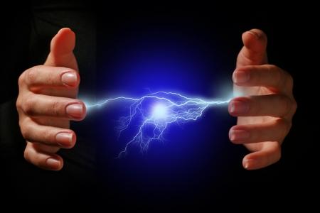 palla di fuoco: Mani e scarica elettrica su sfondo nero.