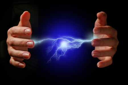 electric shock: Manos y descarga el�ctrica sobre fondo negro.
