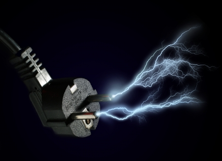 electricity cable: Plug and electric discharge over black background.