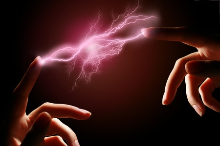 electric spark: Hands and electric discharge over black background.