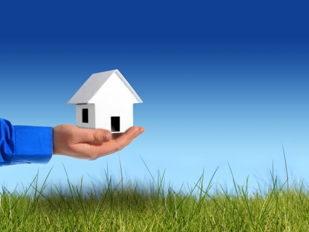 Invest in real estate. Hand with house over sky background.