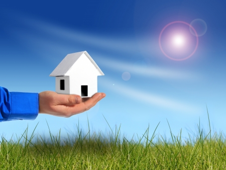 Invest in real estate. Hand with house over sky background. photo