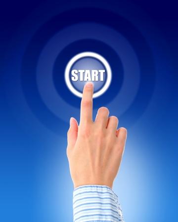 Hand pressing start button over blue background.