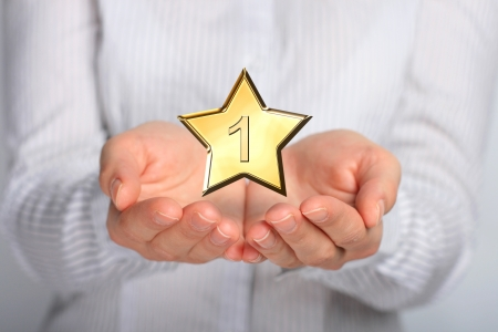 favorite: Golden star in hands  Number one  Stock Photo