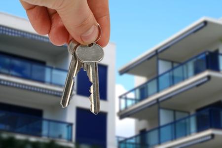 Sleutel in de hand van het appartement over blauwe hemel