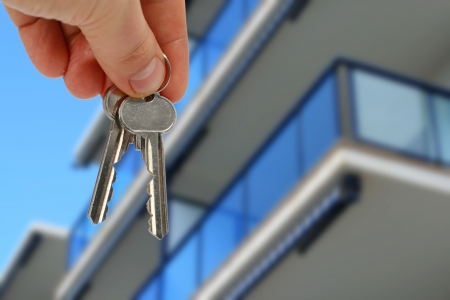 Key in hand from apartment over blue sky