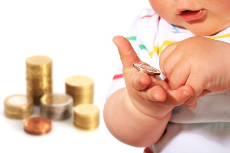 Baby and coin isolated over white.