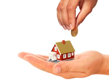 Real estate concept. Hand with coin and house. Stock Photo