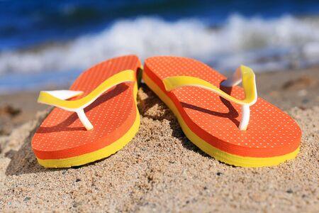 Orange flip-flops in sand on the beach in Barcelona. Stock Photo - 19696179