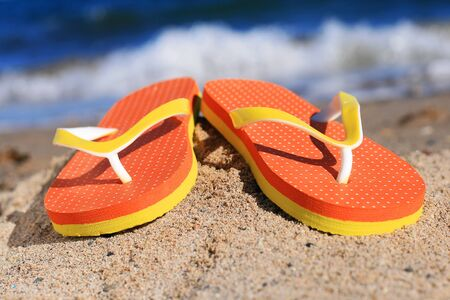 Orange flip-flops in sand on the beach in Barcelona. photo