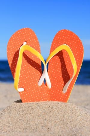 flipflops: Orange flip-flops in sand on the beach in Barcelona.