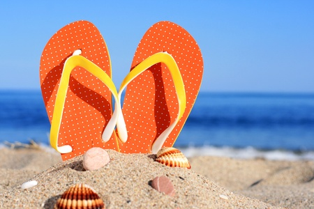 flipflops: Orange flip-flops in sand on the beach in Barcelona
