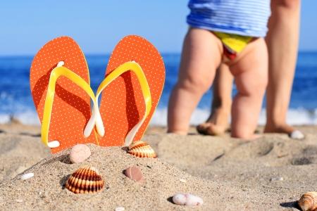 beaches of spain: Orange flip-flops in sand on the beach in Barcelona