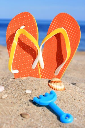 feet in sand: Orange flip-flops in sand on the beach in Barcelona