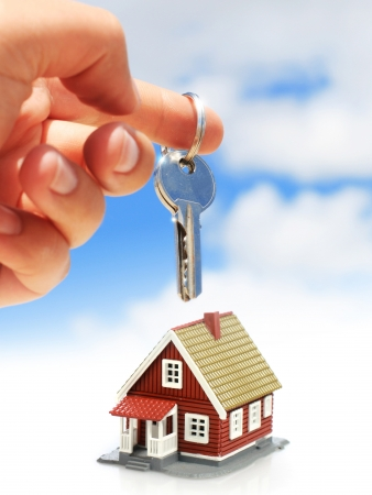 real estate background: Key in hand and house over sky.