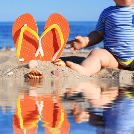 Summer time. Baby and flip-flops on the beach. photo