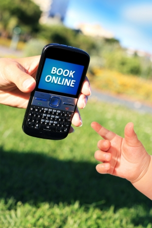 Book online concept. Hands and mobile phone. photo