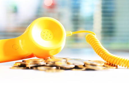 Yellow phone and coins on white table Banque d'images