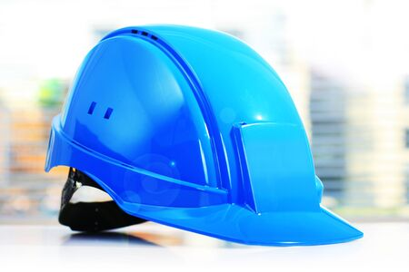 Blue construction helmet on white table. Work safety.