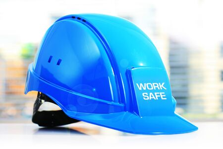 safety at work: Work safe. Blue construction helmet on white table. Stock Photo