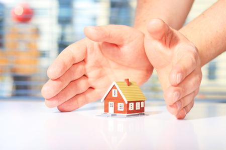 House insurance concept. Hands and little house.