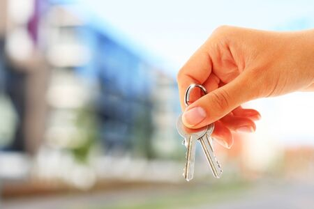 Key in hand and building on the background Banque d'images