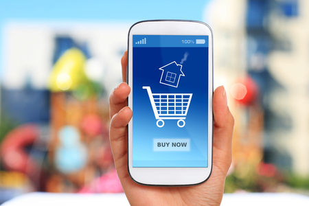 Hand und Handy. Immobilien im Hintergrund. Standard-Bild - 83795550