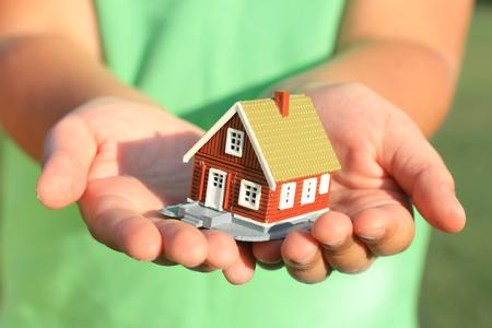 Kid's hand en huis. Onroerend goed op de achtergrond. Stockfoto