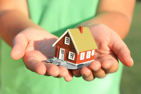Kid's hand and house. Real estate on the background.