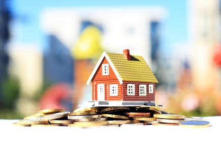 Haus und Münzen . Immobilien auf dem Hintergrund Standard-Bild - 83795553