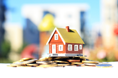House and coins. Real estate on the background.