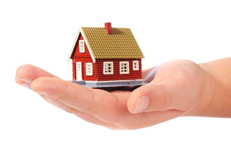 Small cottage in kids hands isolated on white background Banque d'images