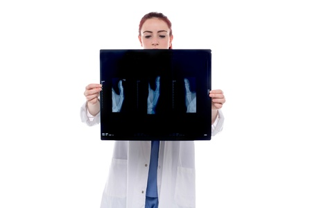 Young female doctor standing inspecting an x-ray which she is holding in her hands as she makes a diagnosis or checks on the progress of a patient, isolated on white photo
